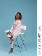 Купить «Beautiful african woman wearing pink clothes and high heels, sitting on a chair. Studio shot.», фото № 28481826, снято 19 ноября 2014 г. (c) Ingram Publishing / Фотобанк Лори