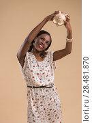 Купить «Portrait of cute african woman posing - holding piggy moneybox», фото № 28481870, снято 19 ноября 2014 г. (c) Ingram Publishing / Фотобанк Лори