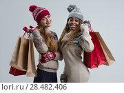 Купить «Shopping, sale, gifts, christmas, xmas concept - two smiling women in knitted dress with shopping bags», фото № 28482406, снято 20 ноября 2014 г. (c) Ingram Publishing / Фотобанк Лори