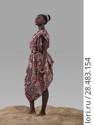 Купить «Attractive young African fashion model standing on sand on gray studio background», фото № 28483154, снято 1 декабря 2014 г. (c) Ingram Publishing / Фотобанк Лори