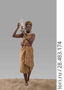 Купить «Attractive young african woman carrying jug with water on sand on gray studio background», фото № 28483174, снято 1 декабря 2014 г. (c) Ingram Publishing / Фотобанк Лори