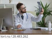 Купить «Thoughtful doctor holding chest and lungs xray in medical office», фото № 28483262, снято 5 июня 2015 г. (c) Ingram Publishing / Фотобанк Лори