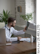 Купить «Thoughtful doctor holding chest and lungs xray in medical office», фото № 28483270, снято 5 июня 2015 г. (c) Ingram Publishing / Фотобанк Лори