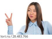 Купить «Portrait of confident young business woman showing victory gesture on white background», фото № 28483766, снято 2 февраля 2013 г. (c) Ingram Publishing / Фотобанк Лори