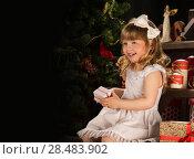 Купить «Happy little girl with Christmas gifts sitting near Christmas tree. Lots of copyspace», фото № 28483902, снято 25 мая 2013 г. (c) Ingram Publishing / Фотобанк Лори