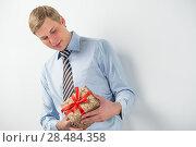 Купить «Smiling businessman holding gift box with red ribbon», фото № 28484358, снято 23 февраля 2013 г. (c) Ingram Publishing / Фотобанк Лори