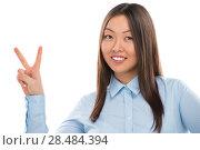 Купить «Portrait of confident young business woman showing victory gesture on white background», фото № 28484394, снято 2 февраля 2013 г. (c) Ingram Publishing / Фотобанк Лори