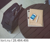 Купить «Business concept, smartphone, papers and pen on table at office building or airport», фото № 28484406, снято 20 июля 2014 г. (c) Ingram Publishing / Фотобанк Лори