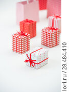 Купить «Gift boxes with xmas presents wrapped in red paper with ornament on white background. Lots of copyspace», фото № 28484410, снято 2 ноября 2012 г. (c) Ingram Publishing / Фотобанк Лори