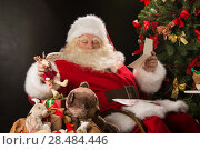 Купить «Santa Claus sitting at home at comfortable armchair holding envelope and reading children's letters and wishes and choosing toys from big sack near him», фото № 28484446, снято 12 января 2013 г. (c) Ingram Publishing / Фотобанк Лори