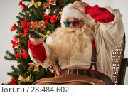 Купить «Santa Claus sitting in rocking chair near Christmas Tree at home and watching tv or home theater wearing 3d glasses and holding remote control», фото № 28484602, снято 19 января 2013 г. (c) Ingram Publishing / Фотобанк Лори