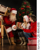 Купить «Santa Claus taking picture of couple with old wooden camera at home near Christmas tree», фото № 28484698, снято 25 мая 2013 г. (c) Ingram Publishing / Фотобанк Лори