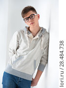 Купить «Portrait of young fashionable man leaning on white wall and wearing glasses. He is trendy fashionable or maybe gay», фото № 28484738, снято 13 апреля 2013 г. (c) Ingram Publishing / Фотобанк Лори