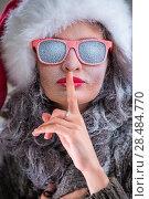 Купить «Woman wearing Santa Claus hat and sunglasses with snow on her face showing silence gesture. Fashion portrait», фото № 28484770, снято 23 сентября 2013 г. (c) Ingram Publishing / Фотобанк Лори