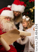 Купить «Santa Claus sitting at home with cute little girl and her mother and reading letter», фото № 28484834, снято 25 мая 2013 г. (c) Ingram Publishing / Фотобанк Лори