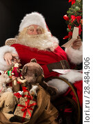 Купить «Santa Claus sitting at home at comfortable armchair holding envelope and reading children's letters and wishes and choosing toys from big sack near him», фото № 28484906, снято 12 января 2013 г. (c) Ingram Publishing / Фотобанк Лори