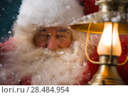 Купить «Santa Claus is holding a shining lantern while sneaking to his home outdoors at North Pole», фото № 28484954, снято 25 сентября 2013 г. (c) Ingram Publishing / Фотобанк Лори