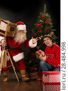 Купить «Santa Claus taking picture of cheerful man with old wooden camera at home near Christmas tree», фото № 28484998, снято 25 мая 2013 г. (c) Ingram Publishing / Фотобанк Лори