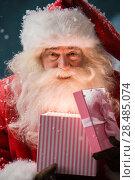 Купить «Happy Santa Claus opening his Christmas gift at North Pole», фото № 28485074, снято 25 сентября 2013 г. (c) Ingram Publishing / Фотобанк Лори