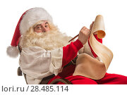 Santa Claus sitting in rocking chair and responding to letter with children wish. Стоковое фото, фотограф Kirill Kedrinskiy / Ingram Publishing / Фотобанк Лори