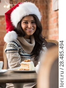 Купить «Beautiful young woman wearing Santa Claus red hat sitting at cafe and having hot beverage and tasty cake», фото № 28485494, снято 24 сентября 2013 г. (c) Ingram Publishing / Фотобанк Лори