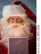 Купить «Portrait of happy Santa Claus opening gift box outdoors at North Pole. Magical light from box on his face», фото № 28485606, снято 25 сентября 2013 г. (c) Ingram Publishing / Фотобанк Лори
