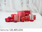 Купить «Gift boxes with xmas presents wrapped in red paper with ornament on light interior background», фото № 28485634, снято 2 ноября 2012 г. (c) Ingram Publishing / Фотобанк Лори