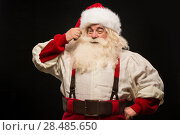 Купить «Photo of happy Santa Claus touching mustache and looking at camera on dark background», фото № 28485650, снято 31 января 2013 г. (c) Ingram Publishing / Фотобанк Лори