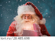 Купить «Happy Santa Claus opening his Christmas gift at North Pole», фото № 28485698, снято 25 сентября 2013 г. (c) Ingram Publishing / Фотобанк Лори