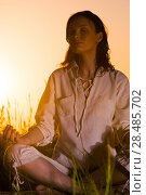 Купить «Beautiful Yoga woman siting against sunrise and rays of sun surrounding her», фото № 28485702, снято 22 июня 2013 г. (c) Ingram Publishing / Фотобанк Лори