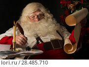 Купить «Santa Claus sitting at home and writing on old paper roll to do list with feather pen and ink at night with candle light. Authentic vintage style portrait.», фото № 28485710, снято 12 января 2013 г. (c) Ingram Publishing / Фотобанк Лори