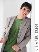 Купить «Happy smiling young man leaning against white wall», фото № 28485966, снято 13 апреля 2013 г. (c) Ingram Publishing / Фотобанк Лори