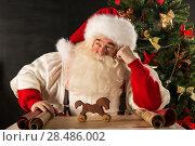 Купить «Santa Claus working - preparing and wrapping christmas gifts, toys before sending it to children», фото № 28486002, снято 31 января 2013 г. (c) Ingram Publishing / Фотобанк Лори