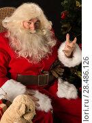 Santa Claus sitting in a comfortable rocking chair near the Christmas tree at home. Стоковое фото, фотограф Kirill Kedrinskiy / Ingram Publishing / Фотобанк Лори