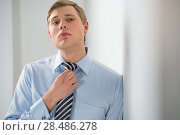 Купить «Portrait of a successful young business man adjusting neck tie», фото № 28486278, снято 23 февраля 2013 г. (c) Ingram Publishing / Фотобанк Лори