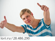 Купить «Closeup of good looking young man gesturing thumbs up sign while leaning on white wall», фото № 28486290, снято 23 февраля 2013 г. (c) Ingram Publishing / Фотобанк Лори