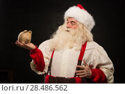 Купить «Santa Claus holding piggy bank moneybox. Christmas budget, banking and credits», фото № 28486562, снято 31 января 2013 г. (c) Ingram Publishing / Фотобанк Лори