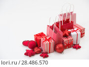 Купить «Gift boxes with xmas presents wrapped in red paper with ornament on white background. Lots of copyspace», фото № 28486570, снято 2 ноября 2012 г. (c) Ingram Publishing / Фотобанк Лори