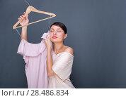 Купить «Portrait of pretty fashionable woman trying new clothes. Fashion poster shot indoors at studio against grey background.», фото № 28486834, снято 30 октября 2011 г. (c) Ingram Publishing / Фотобанк Лори