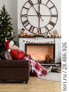 Santa Claus Warming near Fireplace at Home. Стоковое фото, агентство Ingram Publishing / Фотобанк Лори