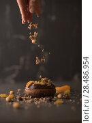 Купить «Chocolate Donut sprinkled with crumbs on dark stone background», фото № 28486954, снято 12 февраля 2015 г. (c) Ingram Publishing / Фотобанк Лори