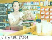 Купить «Female purchaser reviews gift boxes», фото № 28487634, снято 19 апреля 2017 г. (c) Яков Филимонов / Фотобанк Лори