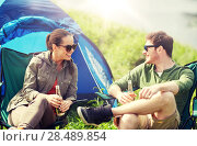 Купить «happy couple drinking beer at campsite tent», фото № 28489854, снято 27 мая 2016 г. (c) Syda Productions / Фотобанк Лори