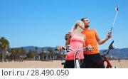 Купить «couple with bicycle and smartphone selfie stick», фото № 28490050, снято 5 июля 2015 г. (c) Syda Productions / Фотобанк Лори
