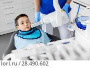 Купить «dentist making x-ray of kid teeth at dental clinic», фото № 28490602, снято 22 апреля 2018 г. (c) Syda Productions / Фотобанк Лори