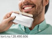 Купить «dentist choosing tooth color for patient at clinic», фото № 28490606, снято 22 апреля 2018 г. (c) Syda Productions / Фотобанк Лори
