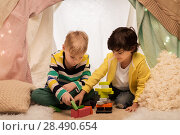 Купить «boys playing toy blocks in kids tent at home», фото № 28490654, снято 18 февраля 2018 г. (c) Syda Productions / Фотобанк Лори