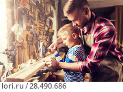 Купить «father and son with hammer working at workshop», фото № 28490686, снято 14 мая 2016 г. (c) Syda Productions / Фотобанк Лори