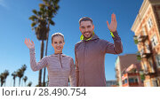 Купить «smiling couple in sport clothes waving hand», фото № 28490754, снято 17 октября 2015 г. (c) Syda Productions / Фотобанк Лори