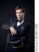 Купить «Magician showing tricks with top hat isolated on dark background», фото № 28491350, снято 19 ноября 2019 г. (c) Ingram Publishing / Фотобанк Лори